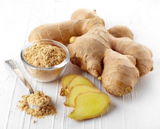 Fresh sliced ginger root and ground ginger on white wooden background